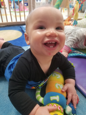 educational toys provide enrichment from the earliest ages. A baby grins as he enjoys some bellytime