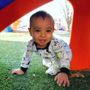 a baby crawls under playground equipment in the playground designed for little ones.